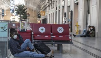 A woman wears a mask to protect against the spread of the coronavirus as she sits next to her luggages at the Gare Saint Lazare train station in Paris, Wednesday, May 6, 2020. France prepares to lift its strict nationwide lockdown on May 11, 2020. (AP Photo/Michel Euler) he