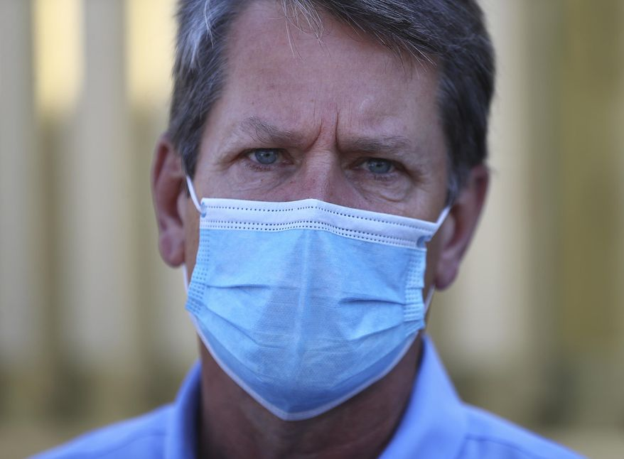 Georgia Gov. Brian Kemp wears a mask and urged fellow citizens to do the same after touring the temporary medical pod that has been placed at the Phoebe North Campus of Phoebe Putney Health System on Tuesday, May 5, 2020, in Albany, Ga. The pod arrived on April 15 and is scheduled to begin operations on Wednesday, May 6, housing 24 beds to treat non-critical COVID-19 patients. (Curtis Compton/Atlanta Journal-Constitution via AP)