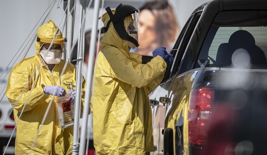 Medical personnel conduct drive-thru COVID-19 testing Monday afternoon May 4, 2020, at Rehoboth McKinley Christian Health Care Services in Gallup, N.M. (Roberto E. Rosales/The Albuquerque Journal via AP)