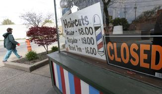 A woman walks past a closed barber shop, Wednesday, May 6, 2020, in Cleveland. (AP Photo/Tony Dejak)