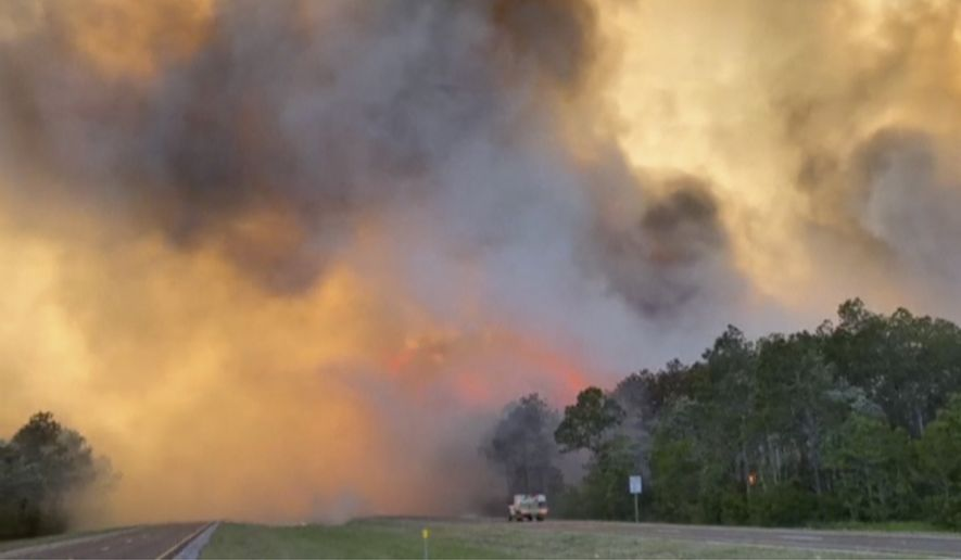 In this image made from video taken May 6, 2020 by the Florida Department of Agriculture and Consumer Services, fire and smoke rise from trees alongside a road in Santa Rosa County, Florida. Wildfires raging in the Florida Panhandle have forced nearly 500 people to evacuate from their homes, authorities said. (Florida Department of Agriculture and Consumer Services via AP)