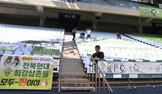 """South Korean club Jeonbuk Hyundai Motors employees display cheer banners from fans at the Jeonju World Cup Stadium in Jeonju, South Korea, Thursday, May 7, 2020. South Korea's soccer league will kick off the season Friday, three days after the first pitch was thrown in baseball, in yet another sign that life in the country is starting to return to normal after strenuous efforts to contain the coronavirus.The sign reads: """"Jeonbuk Hyundai Motors players cheers up."""" (Kim Orel/Newsis via AP)"""