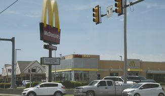 Cars drive by a McDonald's restaurant Thursday, May 7, 2020, in Oklahoma City, where three McDonald's employees suffered gunshot wounds when a customer opened fire because she was angry that the restaurant's dining area was closed because of the coronavirus pandemic, on Wednesday. (AP Photo/Sue Ogrocki)