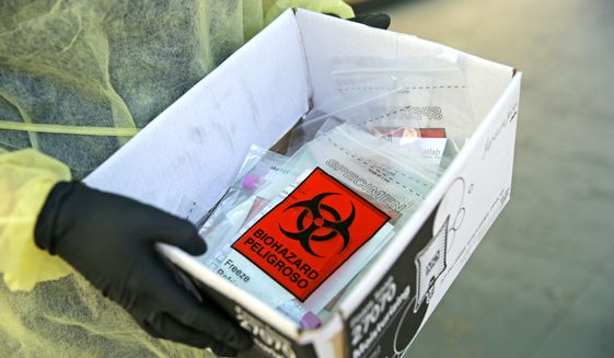 A Florida Department of Health worker holds a box with swab tests from citizens at a COVID-19 testing mobile lab operated by StatLab Mobile at the Residential Plaza for Elderly at Blue Lagoon in Miami during the coronavirus pandemic Thursday, May 7, 2020. (David Santiago/Miami Herald via AP)