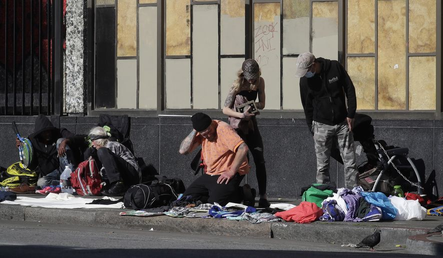 In this April 21, 2020, file photo, people sit and gather with belongings on a sidewalk in San Francisco. There are no tourists anymore on San Francisco's famously twisty and steep Lombard Street. The city's landmark hotels and posh shops are boarded up tight. But one staple of San Francisco has become even more pronounced since the coronavirus pandemic chased everyone inside. The city's homeless continue to sleep on the sidewalks and flap-to-flap in tents cluttered downtown and in other popular neighborhoods. (AP Photo/Jeff Chiu) ** FILE **