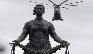 A Mi-26 military helicopter flies over a statue of the Mother Motherland at the Piskaryovskoye Memorial Cemetery where more than half million Leningrad Siege victims were buried during the World War II, during a rehearsal for the Victory Day military air parade which will take place on May 9, in St.Petersburg, Russia, Thursday, May 7, 2020. The Russian air force conducted a rehearsal for the flyover intended to mark the 75th anniversary of the victory over the Nazis on May 9, but the planned military parade is postponed due to the coronavirus outbreak, leaving only the flyby. (AP Photo/Dmitri Lovetsky)