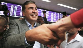 FILE - In this Wednesday, May 29, 2019 file photo, Georgia's ex-President Mikheil Saakashvili, greets his supporters upon his arrival at Boryspil Airport, outside Kyiv, Ukraine. Wednesday, May 29, 2019. Saakashvili said he has accepted Ukrainian President Volodymyr Zelenskiy's offer to become a deputy prime minister in charge of reforms, a move that has angered his home country. (AP Photo/Efrem Lukatsky, FILE)