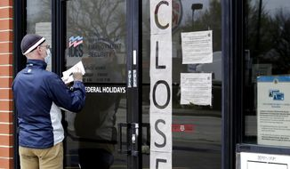 In this April 30, 2020, file photo, a man writes information in front of the Illinois Department of Employment Security in Chicago. (AP Photo/Nam Y. Huh, File)