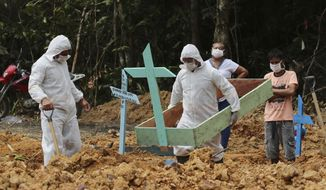 In this Thursday, April 16, 2020 photo, funeral workers in protective gear prepare a grave at the Nossa Senhora Aparecida cemetery, for a woman who is suspected to have died of COVID-19, in Manaus, Amazonas state, Brazil. (AP Photo/Edmar Barros)