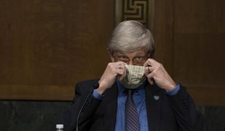 National Institutes of Health Director Dr. Francis Collins puts on his face mask after a Senate Health Education Labor and Pensions Committee hearing on new coronavirus tests on Capitol Hill in Washington, Thursday, May 7, 2020. (Anna Moneymaker/The New York Times via AP, Pool)