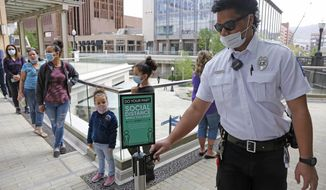 "In this May 6, 2020, file photo, a security guard, right, adjusts a ""Social Distance"" sign as people line up outside the Disney store at City Creek Center in Salt Lake City. Workers are being asked to get shoppers to follow new social distancing protocols like adhering to one-way aisles, keeping their masks on and staying 6 feet away from others to keep everyone safe. (AP Photo/Rick Bowmer, File)"