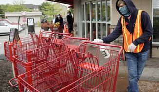 Dilon Moore disinfects shopping carts and controls the number of customers allowed to shop at one time at a Trader Joe's supermarket in Omaha, Neb., Thursday, May 7, 2020. Store workers across the country are suddenly being asked to enforce the rules that govern shopping during the coronavirus pandemic. (AP Photo/Nati Harnik)