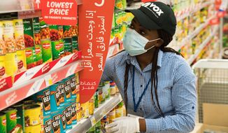 In this April 19, 2020 photo, Vox Cinema employee Jackline Nansamba of Uganda stocks shelves at a Carrefour supermarket while wearing a face mask amid the coronavirus pandemic in Dubai, United Arab Emirates. The coronavirus pandemic has exposed just how vital foreigners are to the Gulf Arab countries where they work as medics, drivers, grocers and cleaners. Vox Cinemas and Carrefour are both owned in the United Arab Emirates by the major retail firm Majid Al Futtaim. (AP Photo/Jon Gambrell)