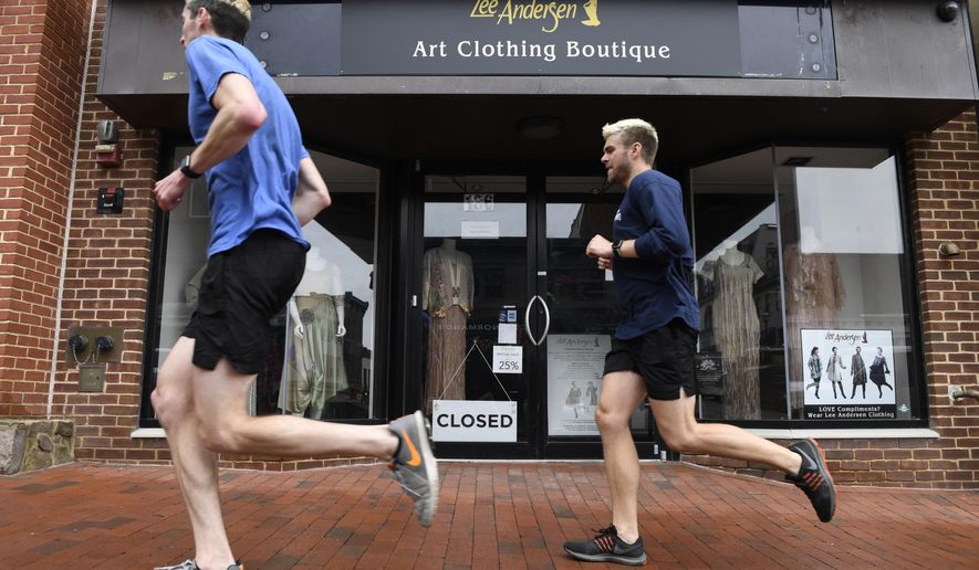 Runners pass a closed business on Main Street in Annapolis, Md., Friday, May 1, 2020. (AP Photo/Susan Walsh)  **FILE**