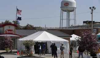 Workers wait in line to enter the Tyson Foods pork processing plant in Logansport, Ind., Thursday, May 7, 2020. The plant was expected to Thursday after closing on April 25 after nearly 900 employees tested positive for the coronavirus. Workers won't be able to return to work until they get tested. (AP Photo/Michael Conroy)