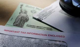 In this April 23, 2020, file photo, President Donald Trump's name is seen on a stimulus check issued by the IRS to help combat the adverse economic effects of the COVID-19 outbreak, in San Antonio. (AP Photo/Eric Gay, File)