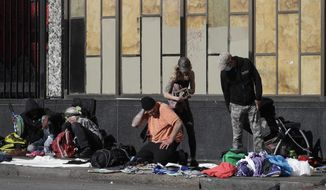 In this April 21, 2020 photo, people sit and gather with belongings on a sidewalk in San Francisco. There are no tourists anymore on San Francisco's famously twisty and steep Lombard Street. The city's landmark hotels and posh shops are boarded up tight. But one staple of San Francisco has become even more pronounced since the coronavirus pandemic chased everyone inside. The city's homeless continue to sleep on the sidewalks and flap-to-flap in tents cluttered downtown and in other popular neighborhoods. (AP Photo/Jeff Chiu)