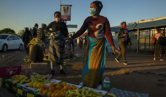 Street vendors, wearing face masks as a precaution against the spread of the new coronavirus, sell fruit on the street corner in Katlehong, east of Johannesburg, South Africa, Wednesday, May 6, 2020. South Africa began a phased easing of its strict lockdown measures on May 1, and its confirmed cases of coronavirus continue to increase as more people are being tested. (AP Photo/Themba Hadebe)