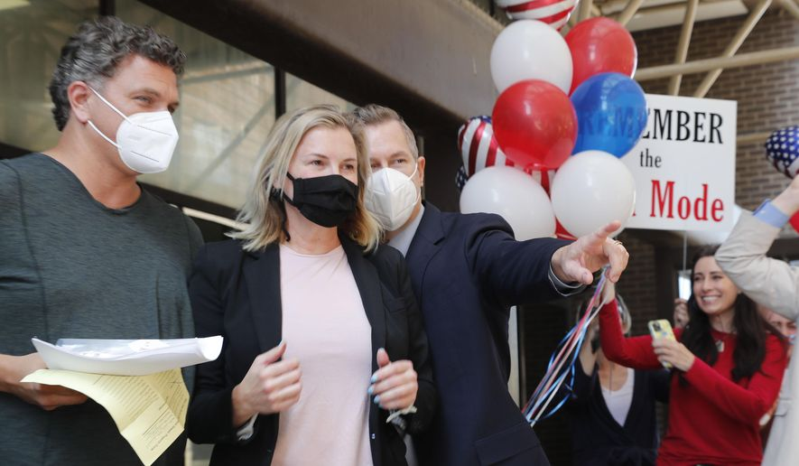 Salon owner Shelley Luther, center right, walks with her boyfriend Tim Georgeff, left, and lawyer Warren Norred after she was released from jail in Dallas, Thursday, May 7, 2020. Luther was jailed for refusing to keep her business closed amid concerns of the spread of COVID-19. (AP Photo/LM Otero)