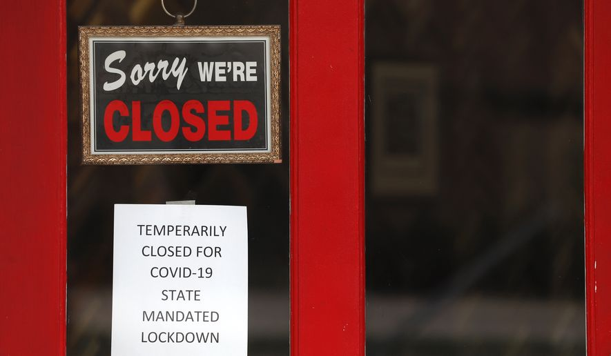 A sign in the widow of The Framing Gallery shows they are closed due to the new coronavirus COVID-19 pandemic, in Grosse Pointe, Michigan, Thursday, May 7, 2020. The U.S. government is poised to report the worst set of job numbers since record-keeping began in 1948, a stunning snapshot of the toll the coronavirus has taken on a now-shattered economy. (AP Photo/Paul Sancya)