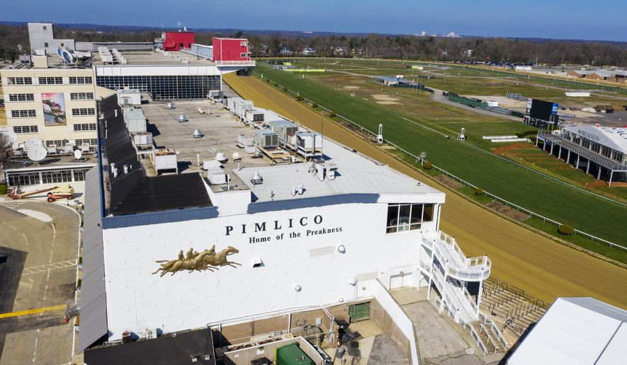 In this March 26, 2020, file photo, tractors groom the racing surface at the Pimlico Race Track in Baltimore, Md. The Preakness will remain at Pimlico Race Course into the foreseeable future, thanks to the passing of a bill to redevelop Maryland's race tracks with $375 million in bonds. (AP Photo/Steve Helber, File) **FILE**