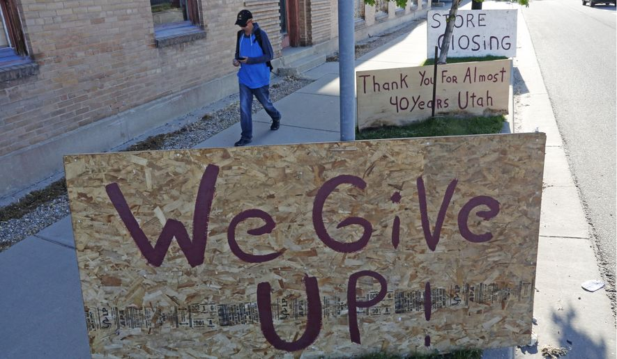 """A man walks past a """"we give up"""" sign outside Euro Treasures Antiques Friday, May 8, 2020, in Salt Lake City. Scott Evans is closing his art and antique store after 40 years. This year started out well for his business, then COVID-19 hit, along with shelter-in-place orders. With a drastic drop in customers, Evans says it was no longer cost effective to stay open. The U.S. unemployment rate hit 14.7% in April, the highest rate since the Great Depression, as 20.5 million jobs vanished in the worst monthly loss on record. (AP Photo/Rick Bowmer)"""