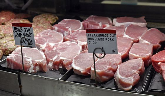Fresh pork chops sit in a case for sale as shoppers look for items on their grocery lists amid the new coronavirus pandemic, Friday, May 8, 2020, at Rouses in Arlington Marketplace in Baton Rouge, La. (Hilary Scheinuk/The Advocate via AP)
