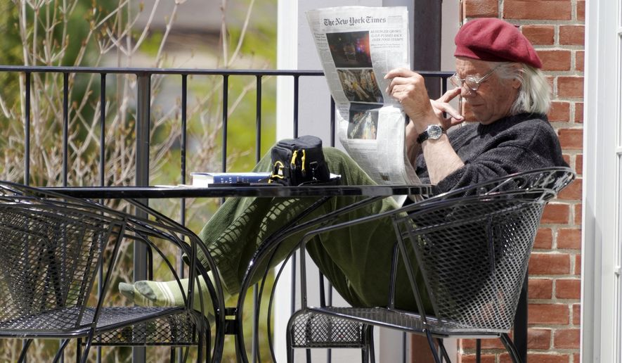 In this Thursday, May 7, 2020, photo, Bob Berkel reads a couple of newspapers during the coronavirus pandemic outside the Stockbridge Library, in Stockbridge, Mass. (Ben Garver/The Berkshire Eagle via AP)