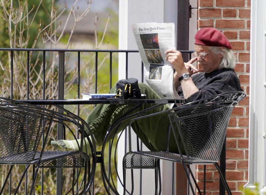 In this Thursday, May 7, 2020, photo, Bob Berkel reads a couple of newspapers during the coronavirus pandemic outside the Stockbridge Library, in Stockbridge, Mass. (Ben Garver/The Berkshire Eagle via AP)