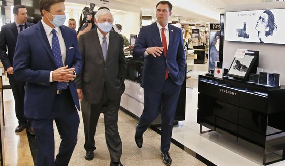 Oklahoma Gov. Kevin Stitt, right, walks with Dillard's Vice President, Bill Dillard III, left, and Dillard's CEO, Bill Dillard II, center, during a tour of Dillard's at Penn Square Mall Friday, May 8, 2020, in Oklahoma City, the fourth day the store has been open since temporarily closing due to coronavirus concerns. (AP Photo/Sue Ogrocki)