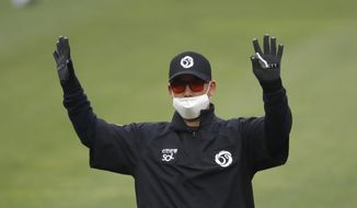Second base umpire Kim Jun-hee wearing a mask and gloves as a precaution against the new coronavirus calls during a baseball game between Hanwha Eagles and SK Wyverns in Incheon, South Korea, Tuesday, May 5, 2020. With umpires fitted with masks and cheerleaders dancing beneath vast rows of empty seats, a new baseball season got underway in South Korea following a weeks-long delay because of the coronavirus pandemic.(AP Photo/Lee Jin-man)  **FILE**