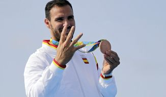 FILE - In this Saturday, Aug. 20, 2016, file photo, Spain's Saul Craviotto celebrates his bronze medal in the men's kayak single 200m final during the 2016 Summer Olympics in Rio de Janeiro, Brazil. It wasn't long ago that Saul Craviotto was sitting in his kayak contemplating a much-anticipated announcement from the Spanish Olympic Committee but now he is among some of the Spanish athletes and sportspeople who have rejoined the police force to help the hard-hit southern European country during the pandemic. He was set to be named the country's flag-bearer for the opening ceremonies in Tokyo. (AP Photo/Matt York, file)
