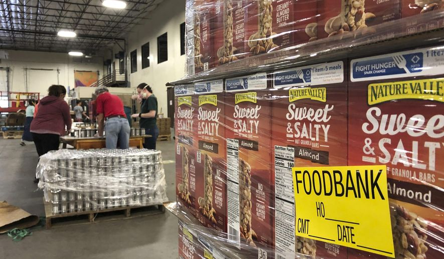 A pallet of food awaits processing as volunteers work in the background to label cans of beans for redistribution at Roadrunner Food Bank in Albuquerque, New Mexico, on Thursday, May 7, 2020. Demand at food pantries has escalated as the number of New Mexicans applying for unemployment benefits increased for the week ending May 2. New Mexico has processed more than 133,000 claims since mid-March. (AP Photo/Susan Montoya Bryan)