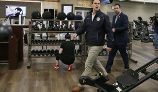 Oklahoma Gov. Kevin Stitt, center, walks through Life Time Athletic as he tours the facility Friday, May 8, 2020, in Oklahoma City, as the facility reopens to the public for the first time since temporarily closing due to coronavirus concerns. (AP Photo/Sue Ogrocki)