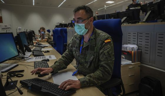 A member of the Spanish army works at the command center during Operation Balmis at the Retamares military base in Pozuelo de Alarcon, outskirts Madrid, Spain, Friday, April 24, 2020. The Opration Balmis coordinates the Spanish army missions during the coronavirus crisis. (AP Photo/Bernat Armangue)