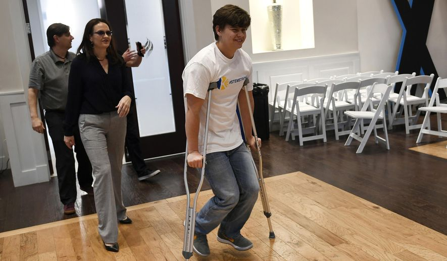 In this May 14, 2019, file photo, shooting victim Josh Jones, arrives on crutches with his parents David, in back, and Lorie, left, before speaking to the media for the first time since the shooting at STEM school in Littleton, Colo. Jones along with fellow student Brendan Bialy helped disarm one of two gunmen that entered their school killing their classmate Kendrick Castillo and wounding others. (Helen H. Richardson/The Denver Post via AP) ** FILE **