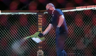 A worker sprays sanitizer in the octagon between bouts during a UFC 249 mixed martial arts competition, Saturday, May 9, 2020, in Jacksonville, Fla. (AP Photo/John Raoux)  **FILE**