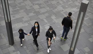 People wear face masks to protect against the spread of the new coronavirus as they walk at an outdoor shopping area in Beijing, Saturday, May 9, 2020. North Korean state media reported on Friday that leader Kim Jong Un sent a personal message to Chinese President Xi Jinping to praise what he described as China's success in getting its COVID-19 epidemic under control. (AP Photo/Mark Schiefelbein)