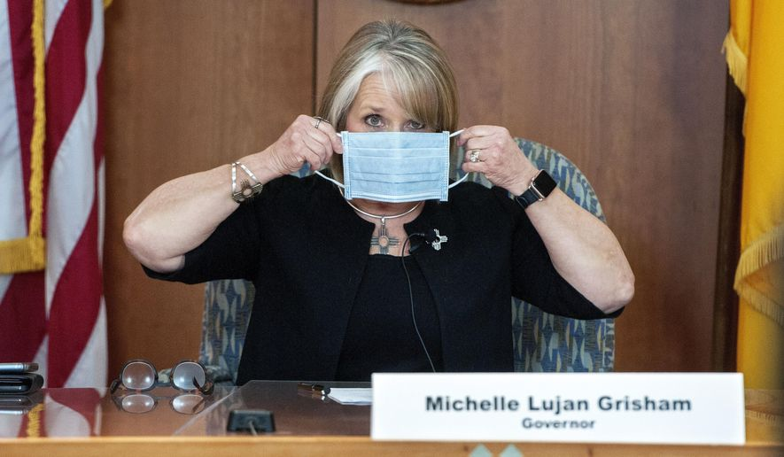 In this April 15, 2020, file photo, New Mexico Gov. Michelle Lujan Grisham puts on her face mask when not speaking during an update on the COVID-19 outbreak in the state during a news conference in the state Capitol in Santa Fe, N.M. (Eddie Moore/The Albuquerque Journal via AP, Pool, File)