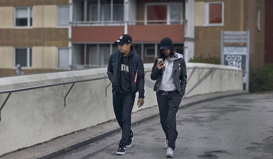 A young couple walks along a bridge in Rinkeby-Kista borough in Stockholm, Sweden, Tuesday, April 28, 2020. The coronavirus has taken a disproportionate toll among Sweden's immigrants. Many in these communities are more likely to live in crowded households and are unable to work remotely. There also are concerns the message has not reached everyone in immigrant neighborhoods. (AP Photo/Andres Kudacki)