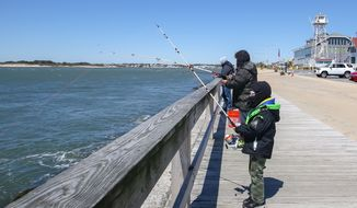 Visitors at the boardwalk at Ocean City, Md., fish while standing six feet apart to follow social distancing guidelines. The resort town reopened its beach and boardwalk on Saturday, May 9, 2020. (Photo by All-Pro Reels / Ed Sheahin)