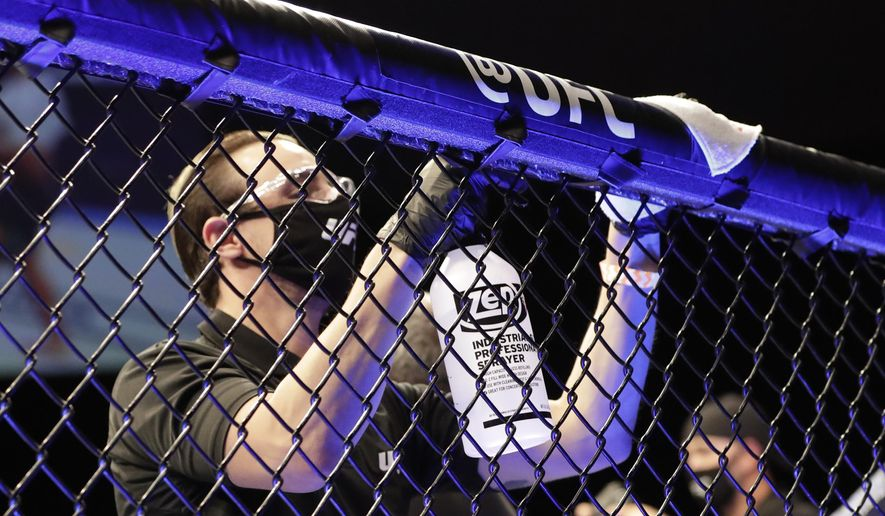A worker wipes down areas of the octagon between bouts at a UFC 249 mixed martial arts event Saturday, May 9, 2020, in Jacksonville, Fla. (AP Photo/John Raoux) **FILE**