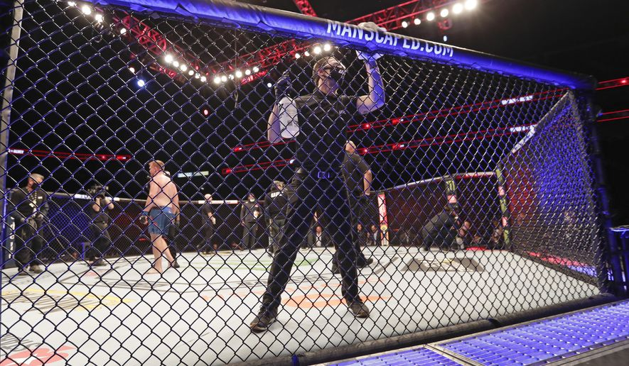 A worker wipes down the octagon between bouts during the UFC 249 mixed martial art event, Saturday, May 9, 2020, in Jacksonville, Fla. (AP Photo/John Raoux)  **FILE**