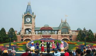 The ceremony for the reopening of the Disneyland theme park is held in Shanghai Monday, May 11, 2020. Visits will be limited initially and must be booked in advance, and the company said it will increase cleaning and require social distancing in lines for the various attractions. With warmer weather and new coronavirus cases and deaths falling to near-zero, China has been reopening tourist sites such as the Great Wall and the Forbidden City palace complex in Beijing.(AP Photo/Sam McNeil)