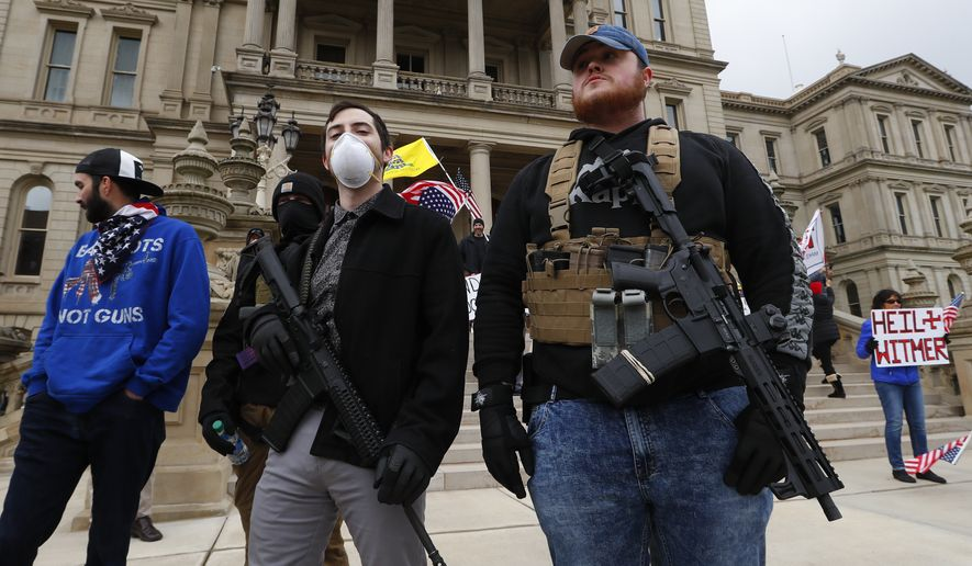 FILE - In this April 15, 2020 file photo, protesters carry guns outside the Capitol Building in Lansing, Mich. A commission that oversees the Michigan Capitol has formed a committee to study whether to ban or restrict guns inside the building. The State Capitol Commission voted Monday, May 11, 2020 to seek input from the Legislature and Gov. Gretchen Whitmer. (AP Photo/Paul Sancya File)