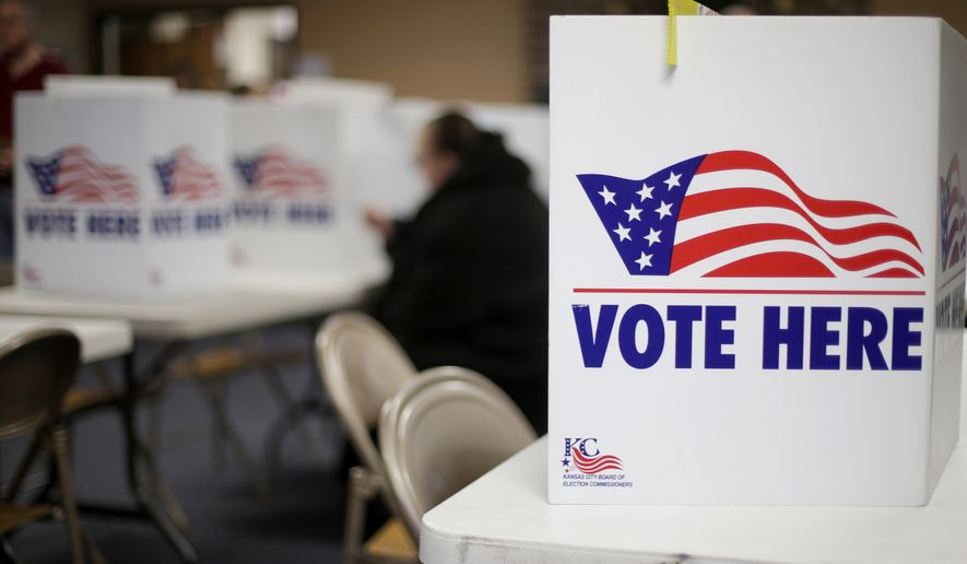 In this March 10, 2020 file photo, a woman votes in the presidential primary election at the Summit View Church of the Nazarene in Kansas City, Mo. (AP Photo/Charlie Riedel, File)