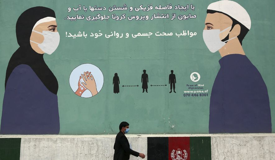 A man wearing a protective face mask to help curb the spread of the coronavirus, walks past a painted wall of Ministry of Public Health, which guides social distancing in Kabul, Afghanistan, Monday, May 11, 2020. (AP Photo/Rahmat Gul)