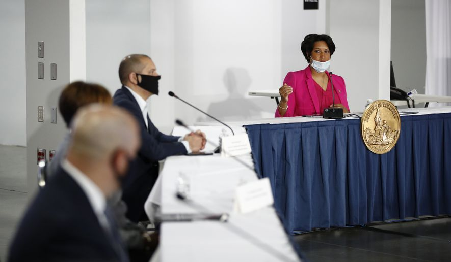 District of Columbia Mayor Muriel Bowser, right, speaks during a news conference at a temporary alternate care site constructed in response to the coronavirus outbreak inside the Walter E. Washington Convention Center in Washington, Monday, May 11, 2020. (AP Photo/Patrick Semansky)