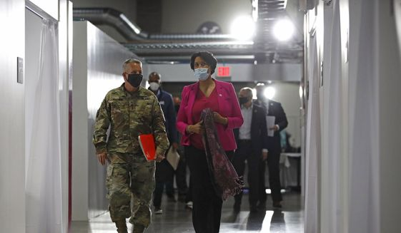 Lt. Gen. Todd Semonite, left, commanding general of the U.S. Army Corps of Engineers, departs a news conference with District of Columbia Mayor Muriel Bowser at a temporary alternate care site constructed in response to the coronavirus outbreak inside the Walter E. Washington Convention Center in Washington, Monday, May 11, 2020. (AP Photo/Patrick Semansky)  **FILE**