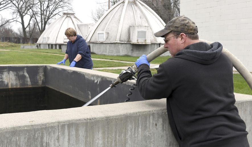 St. Clair, Minn., Public Works employees Thad Baker and Deb McCollum rinse a tank at the city's water treatment plant on April 24, 2020. The two make up the small city's water department, sewer department, streets department and parks department. (Pat Christman/The Free Press via AP)